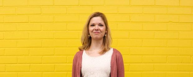 nainen keltainen seinä taustalla